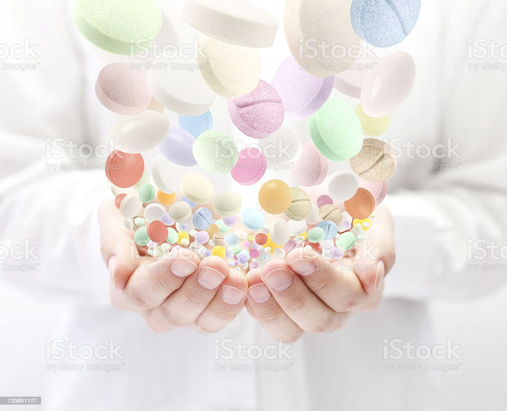 Colorful pills falling into open palms royalty-free stock photo