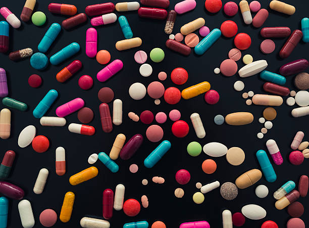 colorful pills on black background - capsule stock photos and pictures