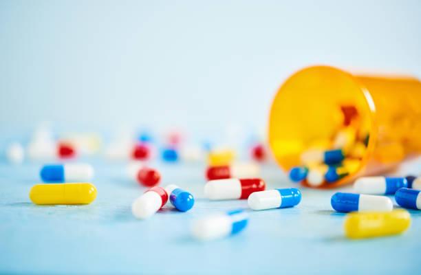 Bunte Pillen mit Pille Flasche auf blauer Tisch – Foto