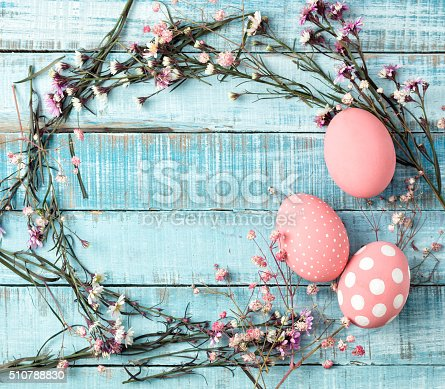 istock colorful pink eggs and flower frame on blue wood 510788830