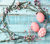 colorful pink eggs and flower frame on blue wood