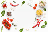 Colorful pizza ingredients. Tomatoes, cheese, chilli peppers and basil leaves on white background, top view, free space
