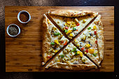 A colorful pizza with herbs on a wooden tray - top view