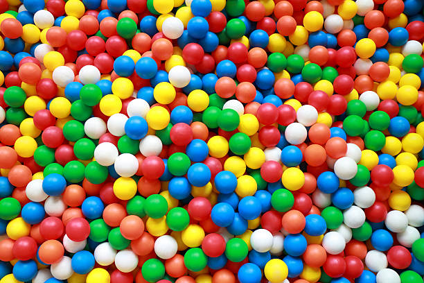 colorful plastic balls in ball pit - competition group stock photos and pictures