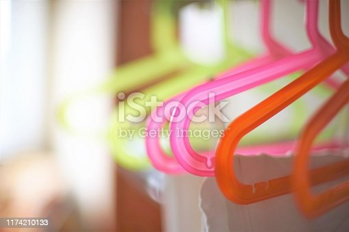 Colorful plastic hangers hanging on the rack.