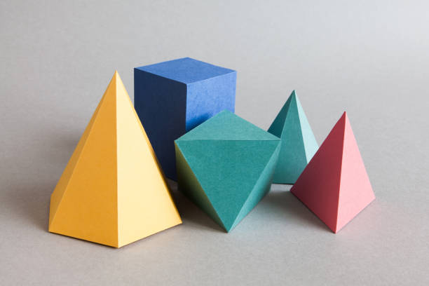 Colorful platonic solids, abstract geometric figures on gray background. Pyramid prism rectangular cube yellow blue pink green colored shapes. Shallow depth of field, copy space - foto de stock