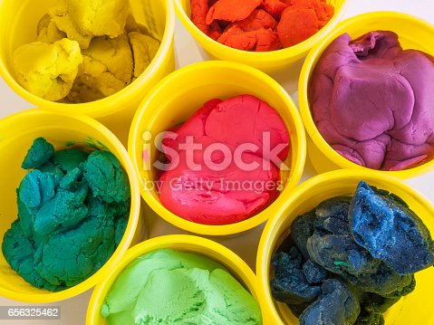 Colorful play dough in yellow cans in white background.