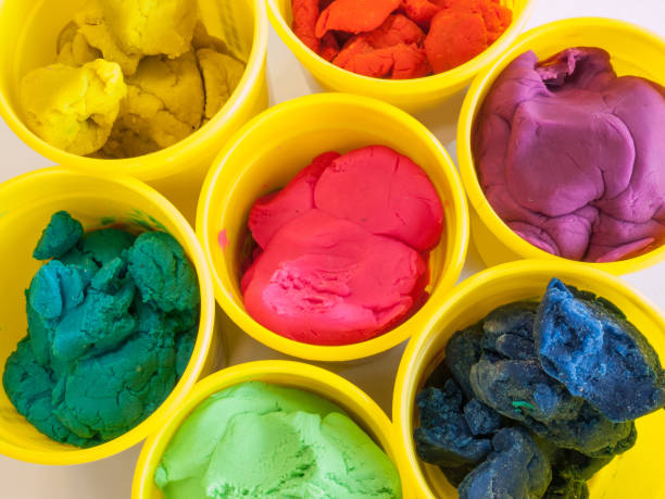 colorful play dough in yellow can Colorful play dough in yellow cans in white background. clay stock pictures, royalty-free photos & images