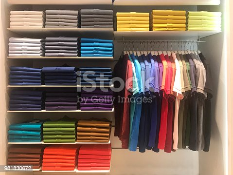 Multi color polo shirts on hanger and shelves for sale in store