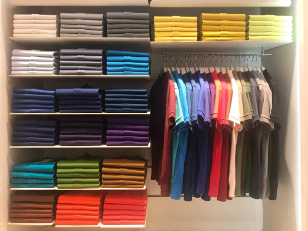 Colorful polo shirts on hanger and shelves in shopping mall Multi color polo shirts on hanger and shelves for sale in store neat stock pictures, royalty-free photos & images