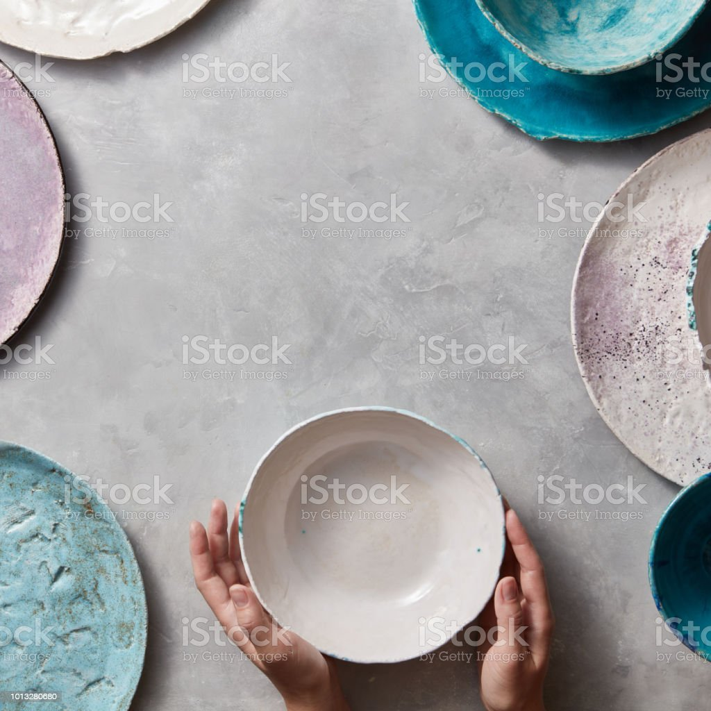 Colorful porceain vintage handmade dishes on a marble table with copyspace. Woman hands take a white ceramic bowl. Top view. stock photo