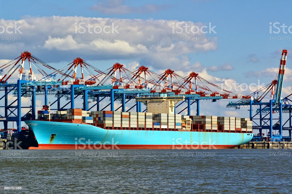 Colorful port facilities with cranes, containers and freight ship stock photo
