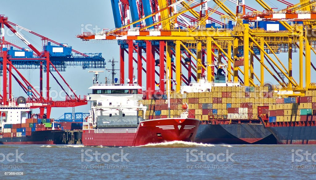 Colorful port facilities with cranes, containers and freight ships stock photo