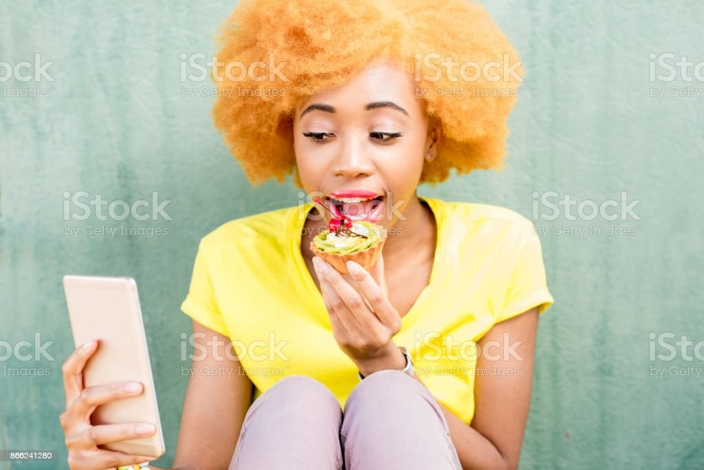 Colorful portrait of an african woman with sweet dessert stock photo