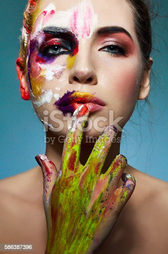 istock Colorful portrait of neon painting over fashion model face. 586387396