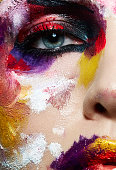 Colorful portrait of neon painting over fashion model face. Half beauty, half creative make up girl. Creativity concept.
