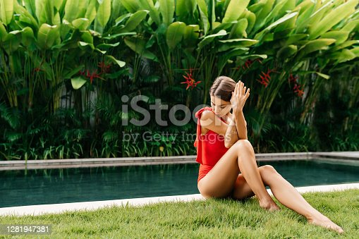 Enjoying suntan and vacation. Colorful portrait of pretty young woman in red swimsuit near swimming pool.
