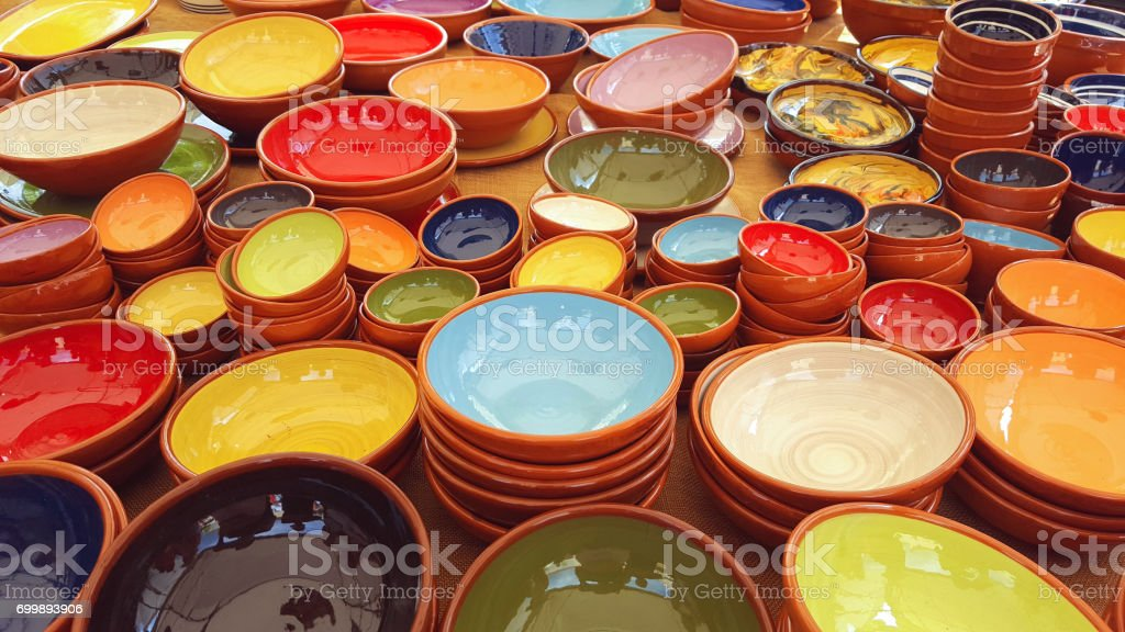 colorful pottery dishes on market stall stock photo