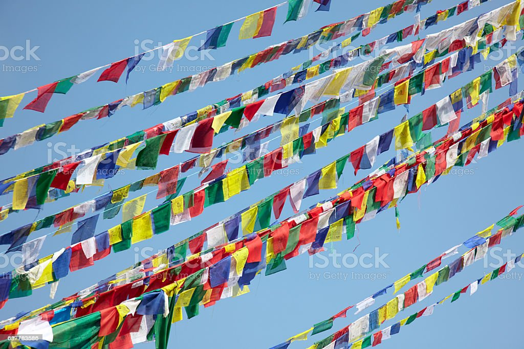 Colorful prayer flags over blue sky background stock photo