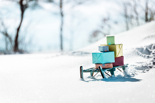 Colorful presents on a wooden sledge standing in the snow, concept christmas and winter season