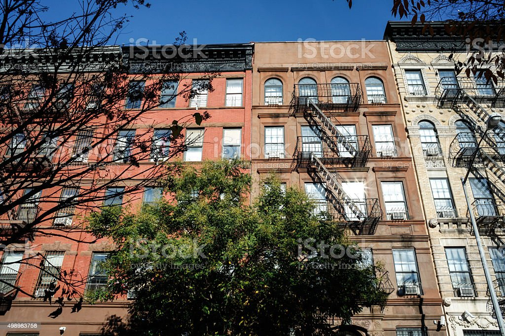 Colorful prewar apartments in the city. Sunshines on colorful prewar apartments on the treelined block. Fire escapes on most buildings.  2015 Stock Photo