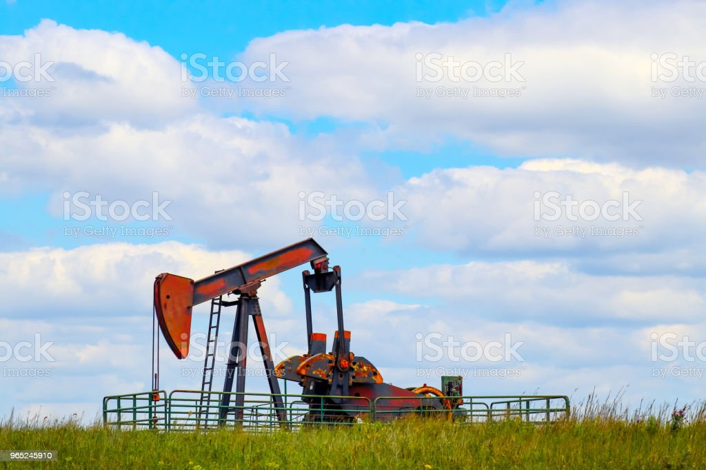 Colorful pump jack on oil well - low horizon on prairie with green grass and wild flowers - big blue cloudy sky - room for text royalty-free stock photo