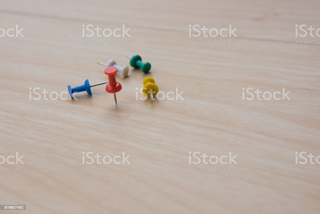 colorful  push pin marking on wooden floor for background stock photo