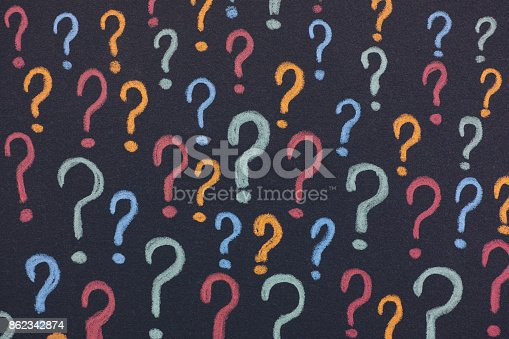 Colorful question marks on a black background. Close up.