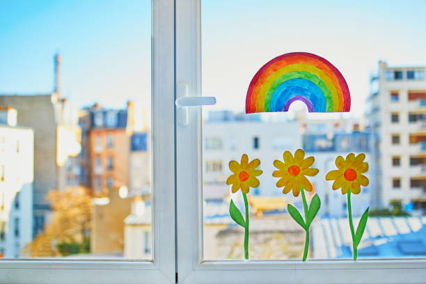 Colorful rainbow and yellow flowers painted on window glass in Parisian apartment stock photo