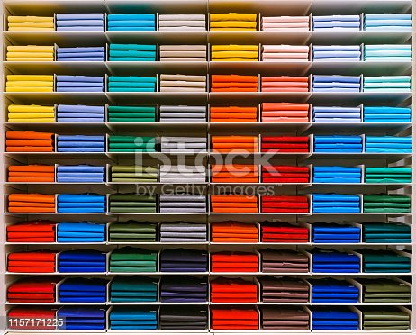 istock Colorful rainbow clothes background .Various vibrant color shirts perfectly folded on a shelf in the shop. Colored male clothes displayed in store. T-shirt of different color are neatly stacked in a row on the store shelves. Color palette: blue, red, oran 1157171225
