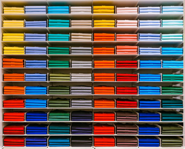 五顏六色的彩虹服裝背景。各種鮮豔的彩色襯衫完美地折疊在商店的架子上。商店裡陳列的彩色男裝。不同顏色的t恤整齊地堆放在商店的貨架上。調色板:藍色、紅色、奧蘭色 - 整齊 個照片及圖片檔