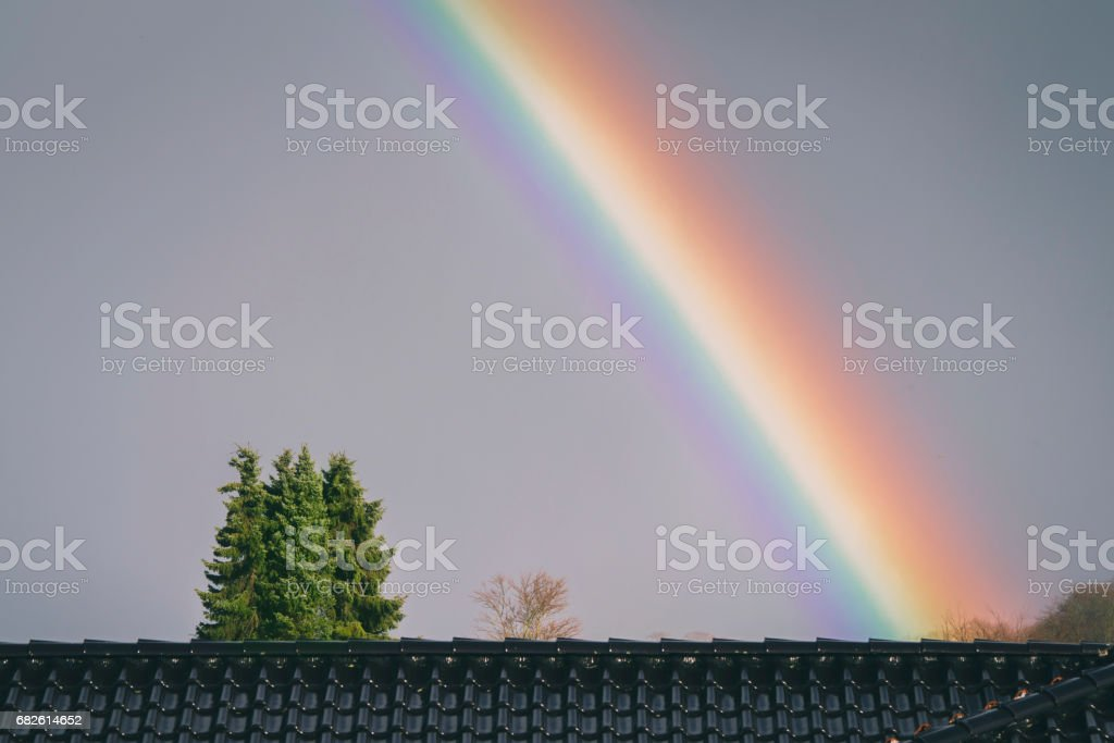 Colorful rainbow over a roof stock photo