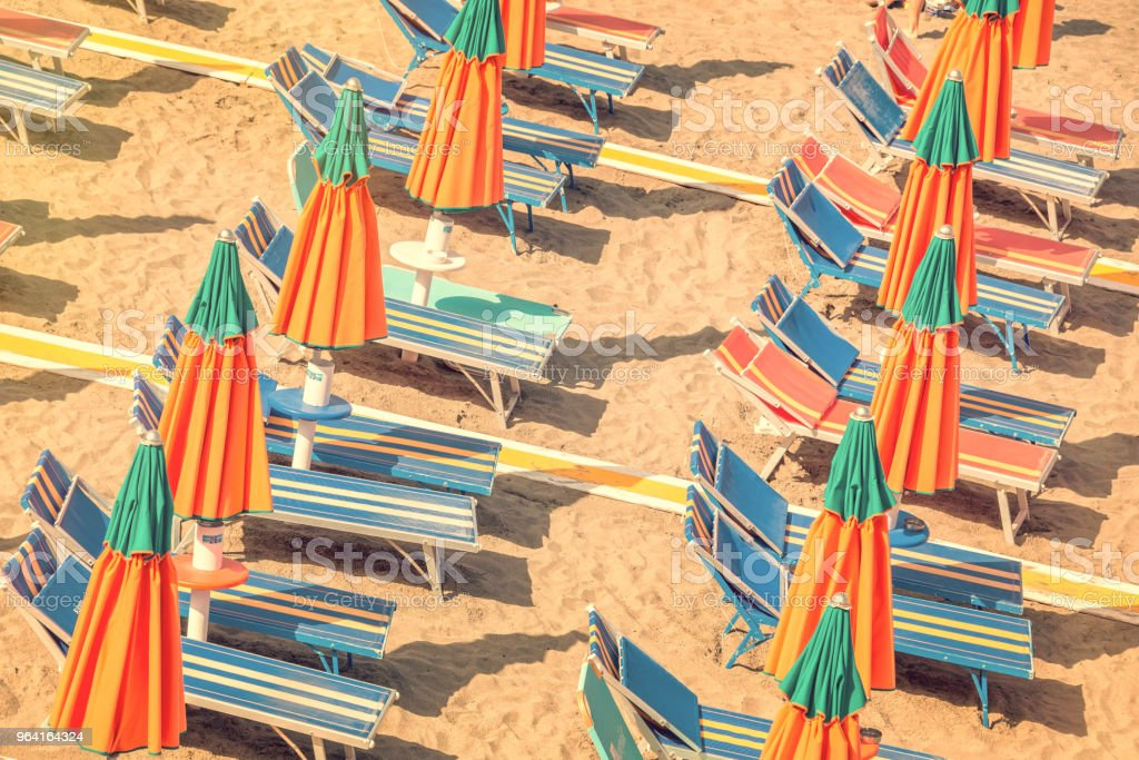 Colorful reclining chairs and parasols on a beach seen from above, vintage process stock photo