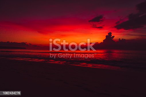 Colorful red bright sunset or sunrise at beach with ocean