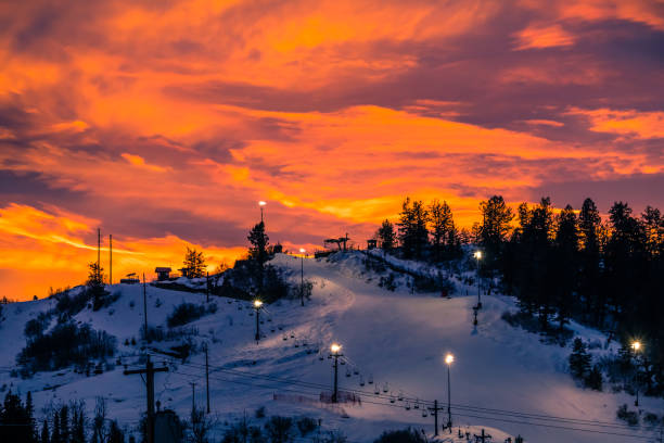 Colorful red sunset over ski slope in Colorado Colorado ski slope with running chairlift at sunset; small figures of people waiting to get up; dramatic sun above the mountain steamboat springs stock pictures, royalty-free photos & images