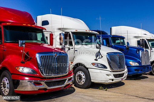 Indianapolis - Circa September 2017: Colorful Red, White and Blue Semi Tractor Trailer Trucks Lined up for Sale XVIII