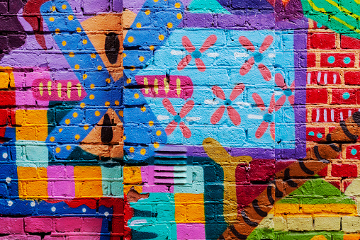 Colorful  street art,  red yellow and bluer graffiti spray painted on a brick stone wall in east part o   Oslo, Norway.