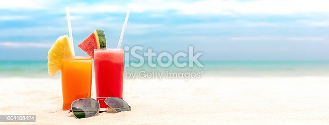 istock Colorful refreshing cold tropical fruit juice drinks in summer beach banner background 1004108424