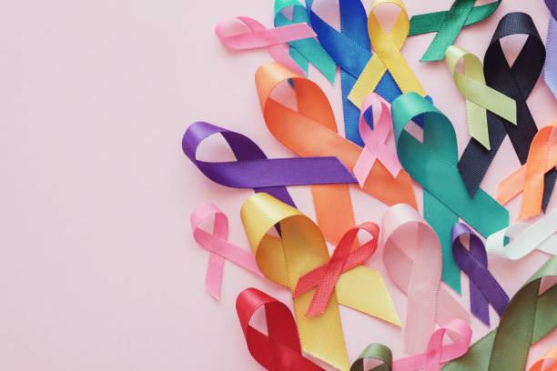bunte bänder auf rosa hintergrund, krebs bewusstsein, weltkrebstag - krebs tumor stock-fotos und bilder