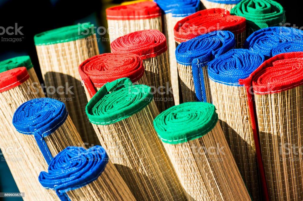 colorful rolled bamboo beach mats closeup stock photo