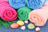 Colorful rolled towels with leaves, soaps and stones closeup picture.