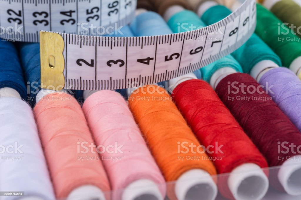 colorful rolls of yarn, sewing thread with cloth measuring tape stock photo