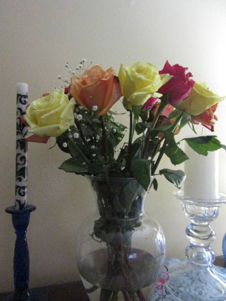Colorful Roses in Vase Next to Candle stock photo