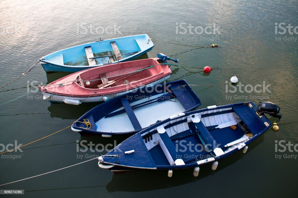 high angle view on row boats in a row isolated on sea, attached by...