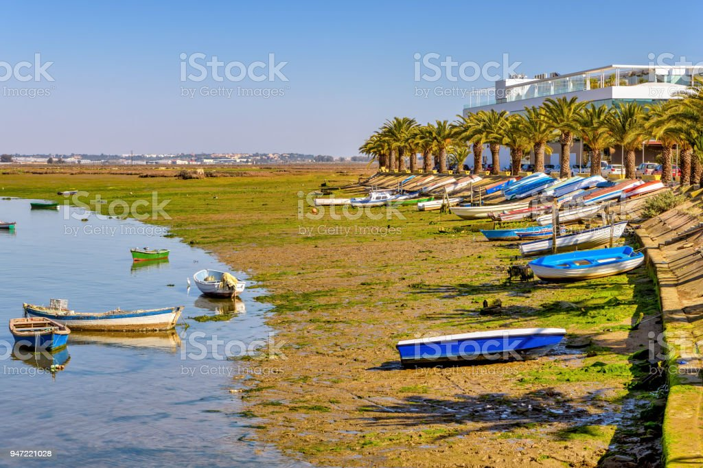 Colorful row boats on the shore of Carreras River in Isla Cristina, Andalusia, Spain. stock photo