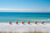 A row of chairs and umbrellas on a white sand beach.