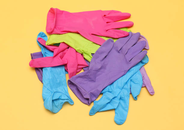 Colorful rubber medical gloves Colorful rubber medical gloves pile on yellow background latex stock pictures, royalty-free photos & images
