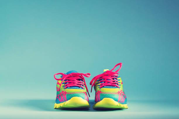 bunte sneakers auf blauem hintergrund ausgeführt - neue sneaker stock-fotos und bilder