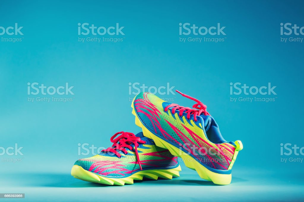 Colorful running sneakers on a blue background stock photo