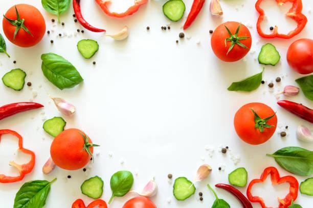 豐富多彩的沙拉配料模式由番茄, 胡椒, 辣椒, 大蒜, 黃瓜切片和羅勒在白色的背景。烹飪理念。頂部視圖。平躺。複製空間 - 烹調原料 個照片及圖片檔
